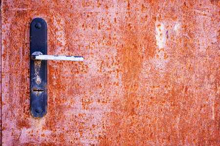 Rusty metal door with the door handle and keyhole close-up. Abstract background. Metallic background.