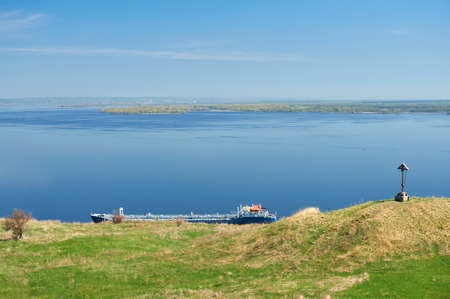 The empty barge near the shore on the background of blue sea and sky.