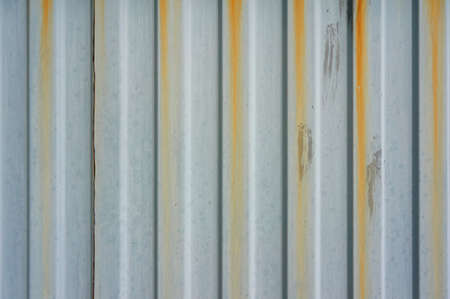 Old corrugated metal wall with rusty streaks. Abstract background.