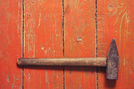 Old hammer on old brown wooden background. Stock Photo