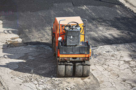 A small orange light machine for laying a new asphalt.