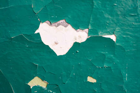 Cracked concrete wall painted green paint. Abstract background.