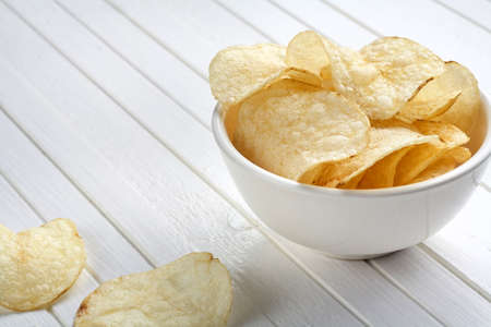 Delicious golden potato chips in a white bowl on a white wooden background. Food background. Stock Photo