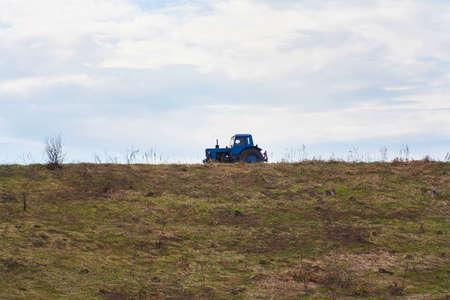 Blue tractor on a background of yellow grass and the sky with clouds.