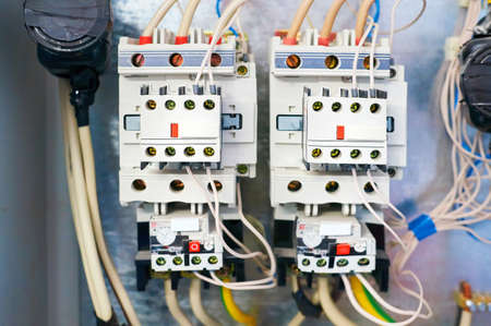 Two electric relays are connected by wires to the metal background.