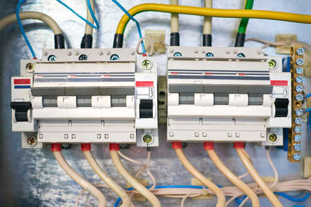 Two electric wires connected trozfaznyh switch on metal background.