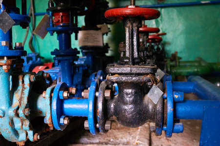Older black with red latch handles on the cold water pipe colored in blue.