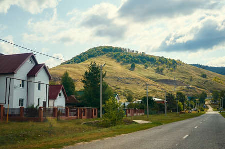 A small town near the hill with an asphalt road. Forest conservation area.