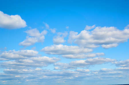 Wavy, porous curly clouds on the blue sky. Nature background.