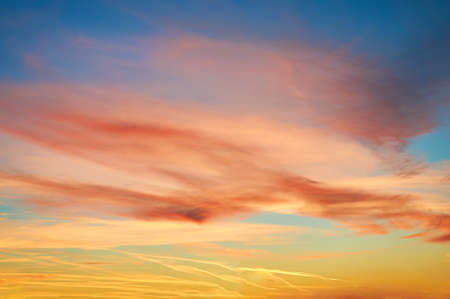 Colored porous clouds at sunset against blue sky. Stok Fotoğraf