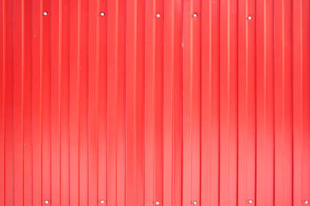 Texture of a metal fence from the profile of a red sheet with vertical lines. Reklamní fotografie