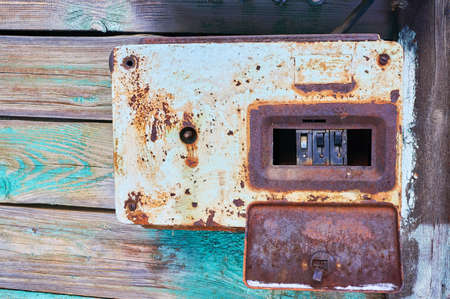 An old and rusty electric circuit breaker placed on a wall in a rusty metal box