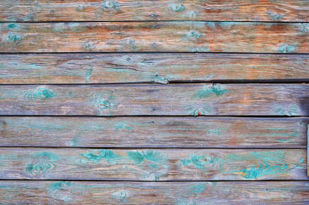 Old wooden painted green paint shield with cracks and scratches.