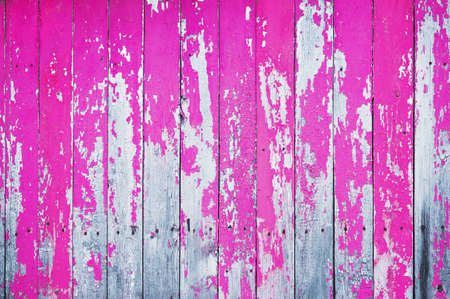 Old cracked wooden board painted with pink paint. Abstract background.