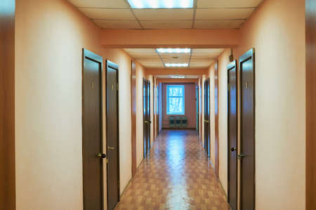 Perspective view of old school or office building hallway corridor, empty narrow, tall and long death end walkway with many doors room and windows. Reklamní fotografie