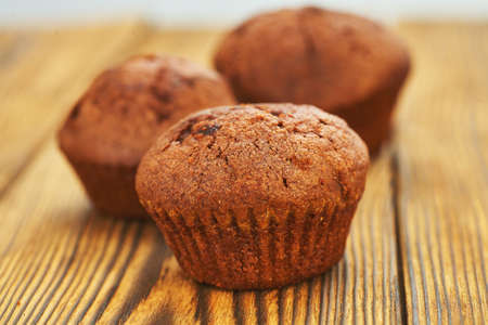 Chocolate muffin with dark background test on an old wooden table. Reklamní fotografie