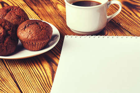 Several chocolate muffins with dark pastry with a cup of coffee and a notepad on a wooden table.
