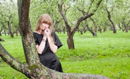nestled: The girl nestled on a tree in park