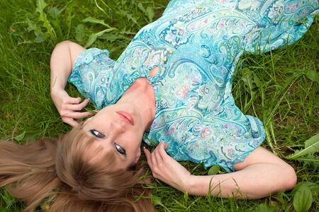 The girl on a grass in a turquoise dress