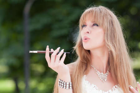 The woman and a mouthpiece with a cigaret photo