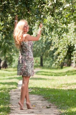 The woman walks barefoot in a green garden photo