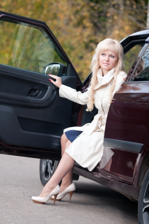 The beautiful woman in a raincoat leaves the car Stock Photo