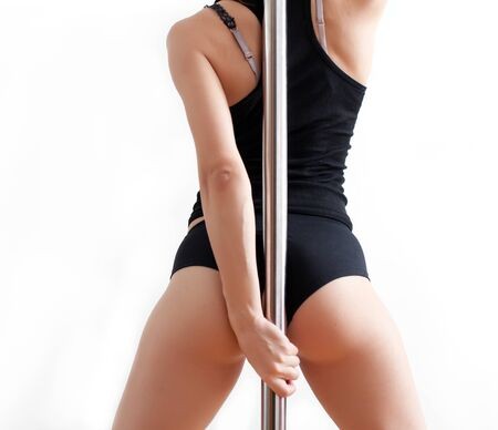 female stripper: Back of the young woman near a pole
