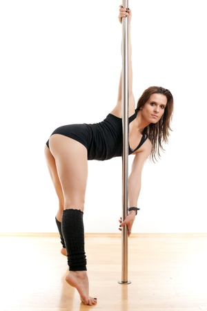 The young beautiful woman is engaged at a pole   photo