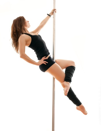 The young beautiful woman hangs on a pole photo