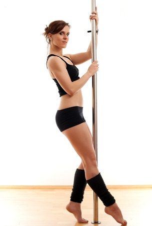 The beautiful young woman dances and keeps for a pole photo