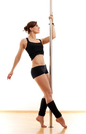 stripper pole: The beautiful young woman dances and keeps for a pole