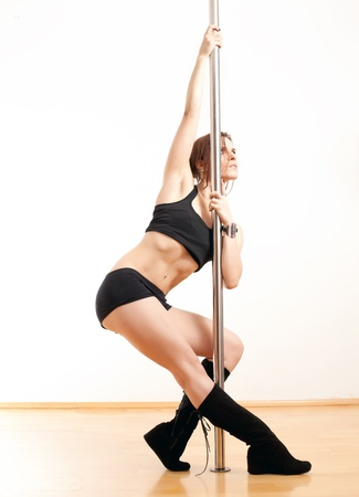 The sports young woman and dancing pole