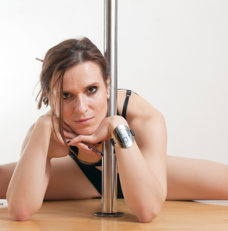 female stripper: The young beautiful woman is engaged at a pole Stock Photo