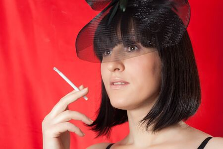 The glamour woman in a black hat smokes a cigaret photo