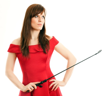 domination: woman in a dress holding a riding crop