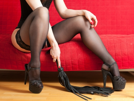 domination: woman in stockings and whip