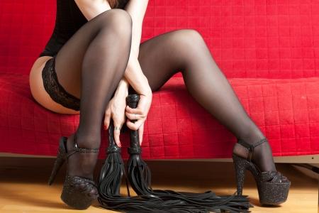 corsetto: donna in calze e frusta Archivio Fotografico