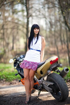 A girl is standing next to a motorcycle photo