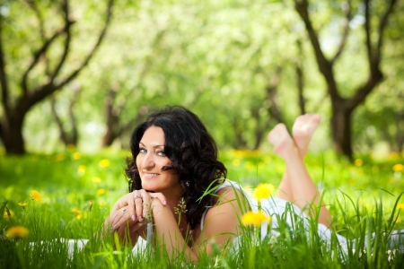 adult beautiful woman lying on the grass photo