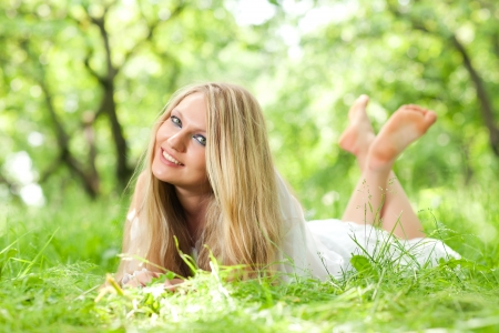 young woman with long hair lying on the grass photo