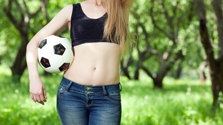 woman holding a soccer ball while standing outdoors  photo