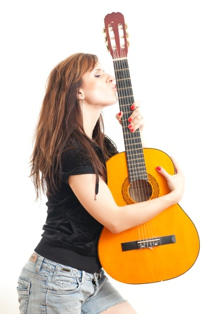 beautiful young woman holding a guitar on a white background photo
