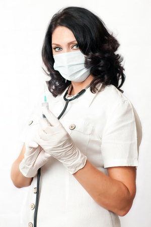 beautiful adult nurse and a white lab coat holding a disposable syringe photo