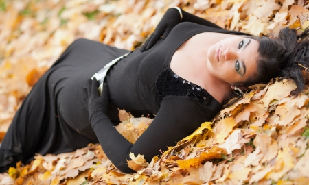 Young beautiful gothic gir in black lying in autumn leaves photo