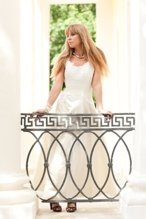 beautiful girl in a wedding dress near pillars. woman in a long white dress with pearls photo