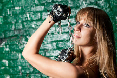 beautiful woman with an steel chain on the background wall Stock Photo - 21305108
