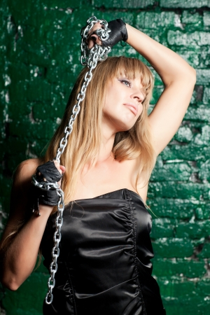 sadomasochism: beautiful woman with an steel chain on the background wall