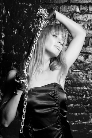 beautiful woman with an steel chain on the background wall Stock Photo - 21305113
