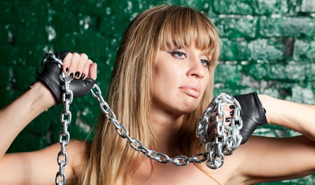 beautiful woman with an steel chain on the background wall