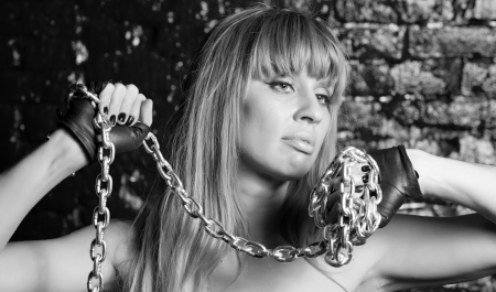 beautiful woman with an steel chain on the background wall Stock Photo - 21305115